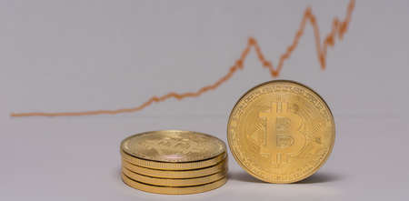 single bitcoin stands next to a stack of bitcoins with a stock market chart panorama view