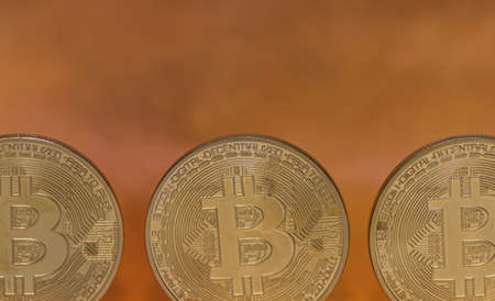 three bitcoins and orange background detail view
