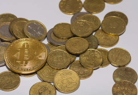 many euro coins and one golden valuable bitcoin in the middle left view 写真素材