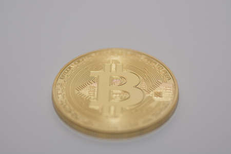 one single golden bitcoin lying on a gray background middle bottom view