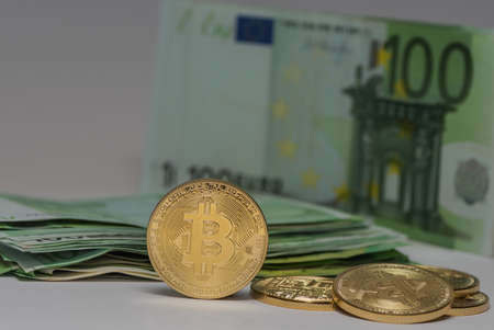 standing valuable bitcoin next to others with many 100 euro bills