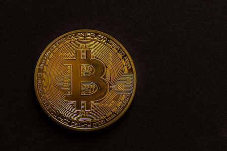 single golden shiny valuable bitcoin front view with black left view 写真素材