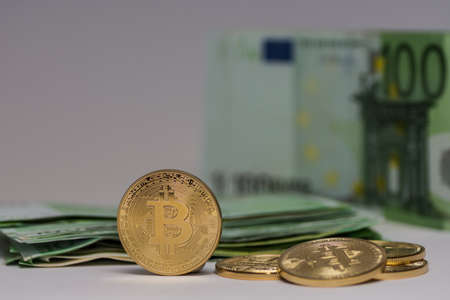 standing bitcoin next to others with many 100 euro bills detail view