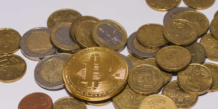 many euro coins and one golden valuable bitcoin in the middle view 写真素材