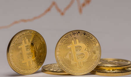 golden bitcoins with a rising stock market chart in the background detail view 写真素材