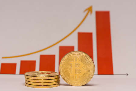 single bitcoin stands next to a stack of bitcoins with a rising stock market chart in the background middle view