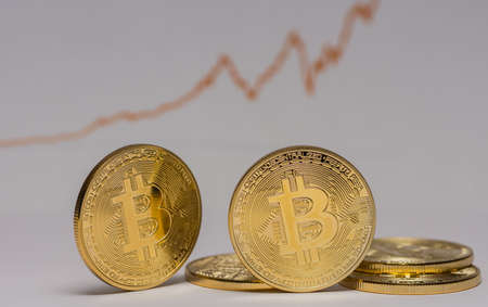 golden bitcoins with a rising stock market chart in the background with gray 写真素材