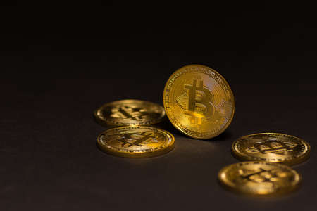 golden shiny expensive bitcoins  lying on black background right view