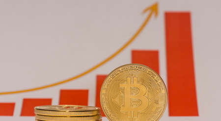single bitcoin stands next to a stack of bitcoins with a rising stock market chart panorama view