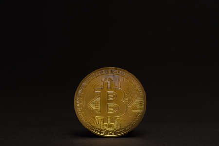 single golden shiny valuable bitcoin standing on a black background middle bottom view 写真素材