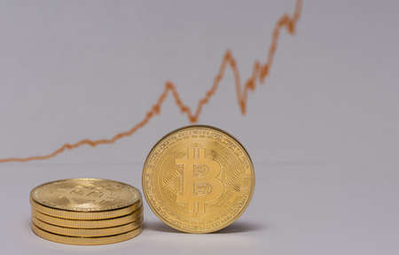 single bitcoin stands next to a stack of other bitcoins with a stock market chart in the background
