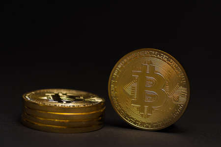 stack of golden shiny valuable bitcoin standing on a black background detail view