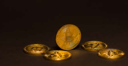 golden shiny expensive bitcoins  lying on black panorama view