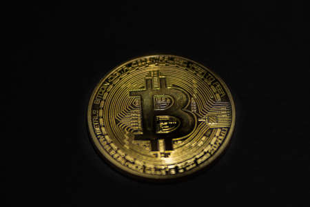 single golden valuable bitcoin on black background in the middle view
