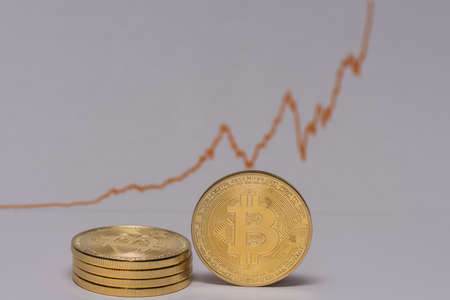 single bitcoin stands next to a stack of bitcoins with a stock market chart middle view
