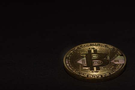 single golden valuable bitcoin on black background right bottom view 写真素材