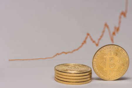 single bitcoin stands next to a stack of bitcoins with a stock market chart right view