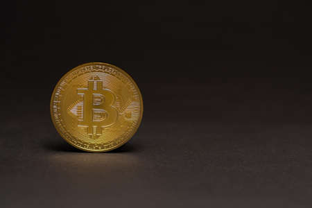 single golden shiny valuable bitcoin standing on a black background left view 写真素材