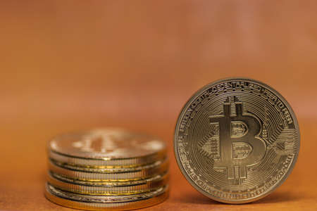 one bitcoin and other stacked with orange background detail view