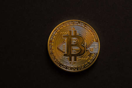 single golden shiny valuable bitcoin front view with black middle view
