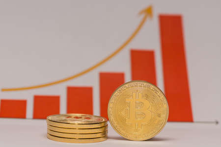 single bitcoin stands next to a stack of bitcoins with a rising stock market chart middle view 写真素材