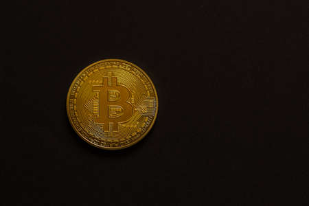 single golden shiny valuable bitcoin front view with black background left and middle