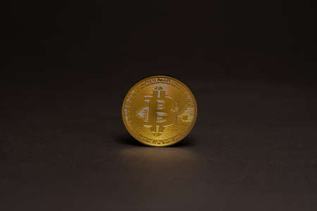single golden shiny valuable bitcoin standing on a black background in the middle view