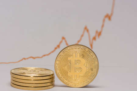 single bitcoin stands next to a stack of other bitcoins with a stock market chart