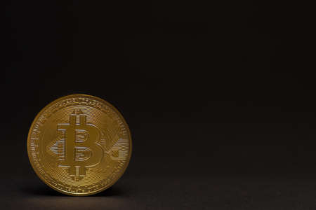 single golden shiny valuable bitcoin standing on a black background left bottom view