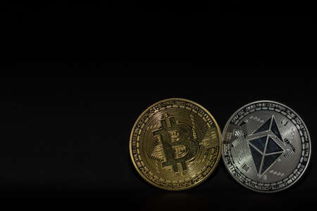 single bitcoin and ether coin with black background bottom right view