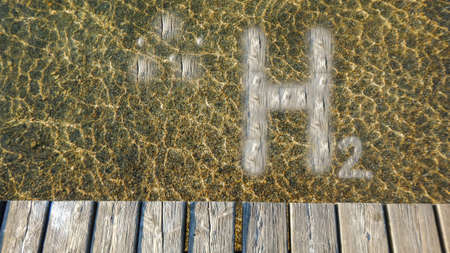 wooden h2 hydrogen letters in the water with waves near a wooden jetty