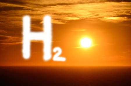shining white h2 hydrogen letters with bright orange sunset at the sea
