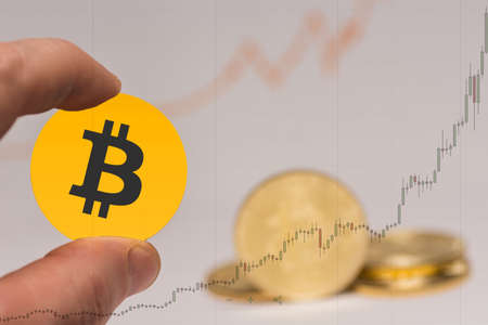valueable orange bitcoin sign held between two fingers and a rising chart in_the_background