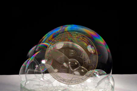 valueable golden bitcoin crypto currency behind colorful soap bubbles bevor bursting