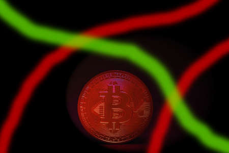 valueable red hot bitcoin crypto currency standing on a dark background and green red stripes Banque d'images