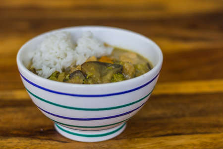 fresh healthy thai green curry and chicken in a bowl on a table