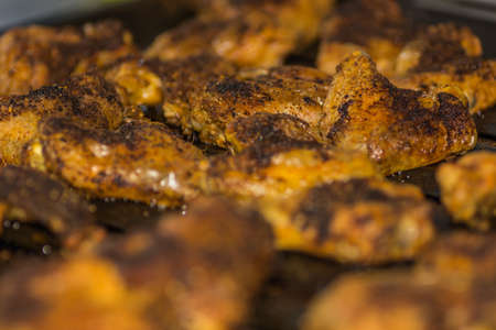 many grilled tasty chicken wings on a pan detail view