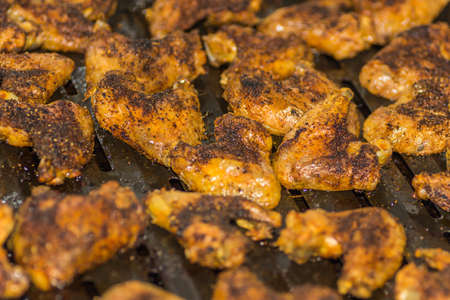 many golden grilled tasty chicken wings on a pan while cooking Foto de archivo