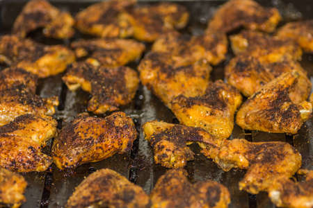 many grilled tasty chicken wings on a pan while cooking