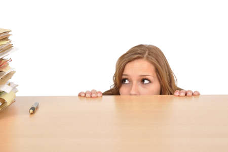 Young woman hiding behind the desk photo