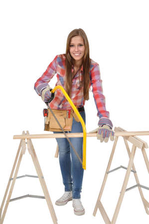 young woman with a hacksaw sawing a board Stock Photo