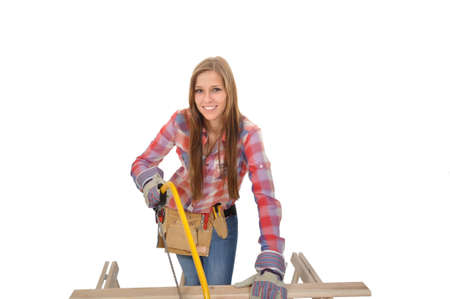 young attractive handyman with hacksaw sawing a board Stock Photo