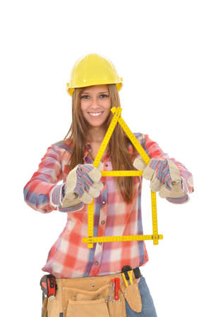 young attractive woman builds a house from a yellow ruler