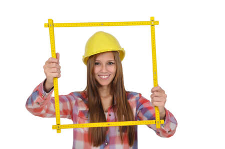 young attractive woman with a yellow helmet looks through a measuring stick