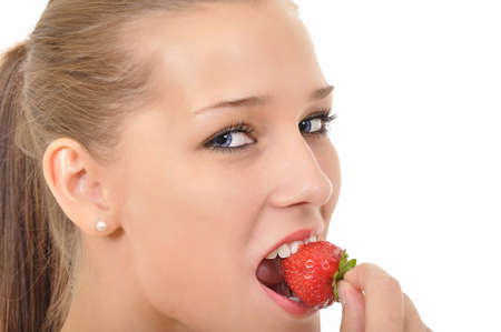 young woman with blue eyes biting into a strawberry