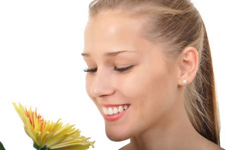 attractive young woman smelling a yellow flower Stock Photo
