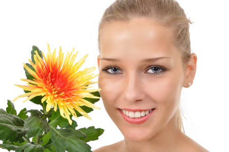 smiling young woman with blue eyes shows a flower