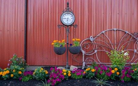 Flowers in garden at dusk with clock