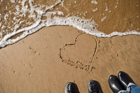 fingered drawn heart on a beach  photo