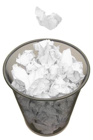 wastepaper basket: cesto pieno di carta straccia su sfondo bianco puro